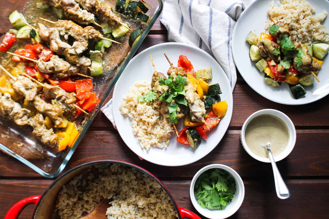 spread of chicken satay with colorful bell peppers and zucchini