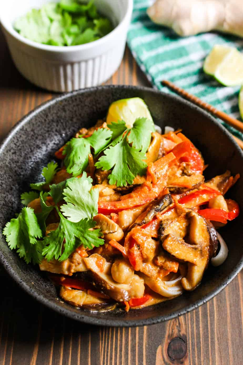 bowl of thai red curry soup with bell peppers and mushrooms
