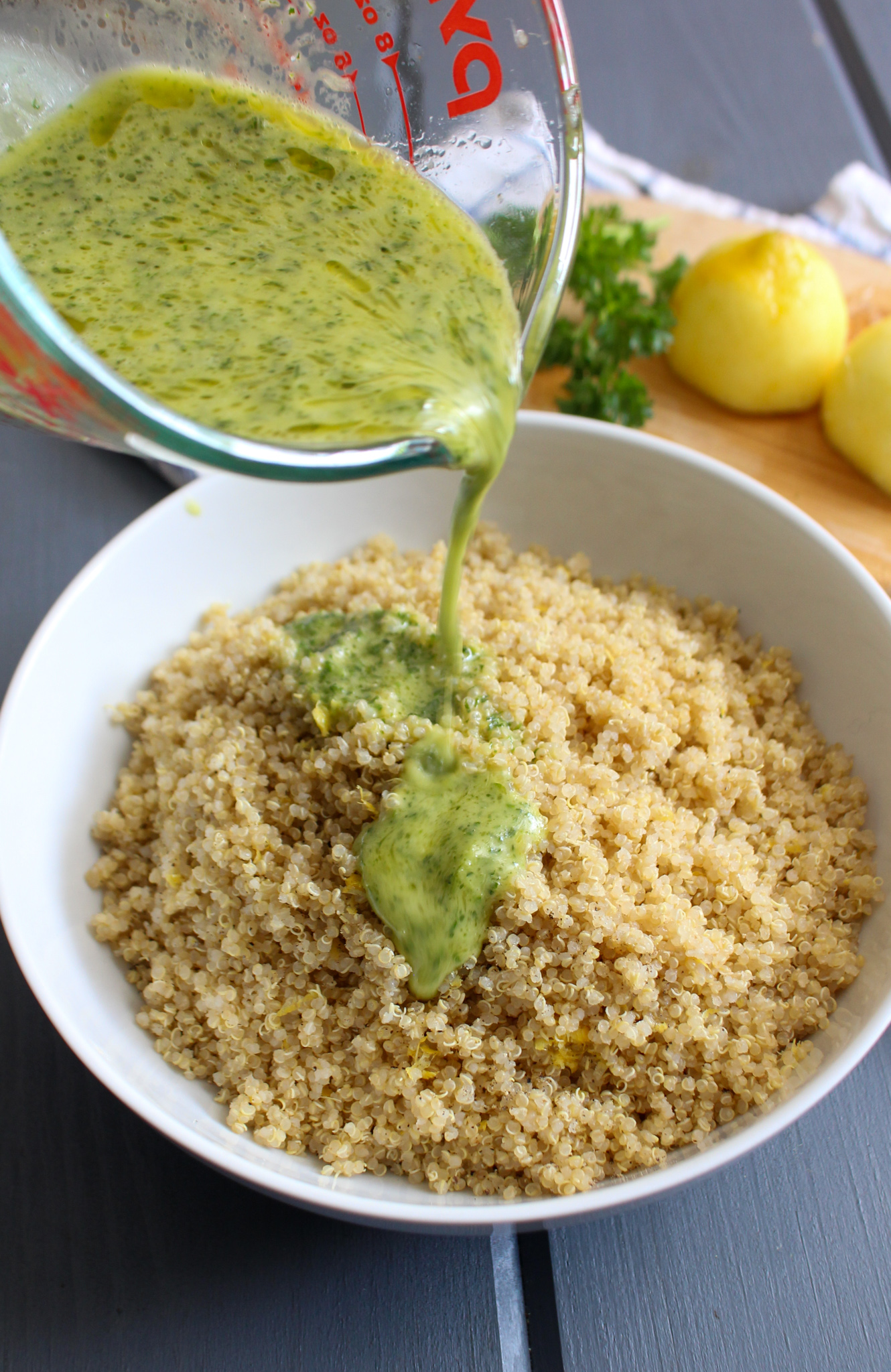 Pouring lemon parsley dressing over lemon quinoa