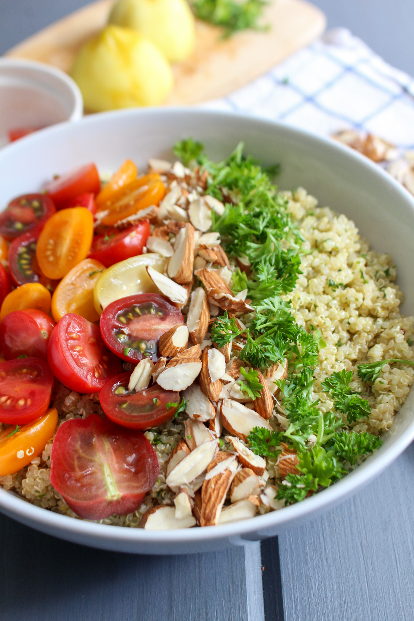 Bowl of quinoa salad with parsley, almonds, and tricolor grape tomatoes