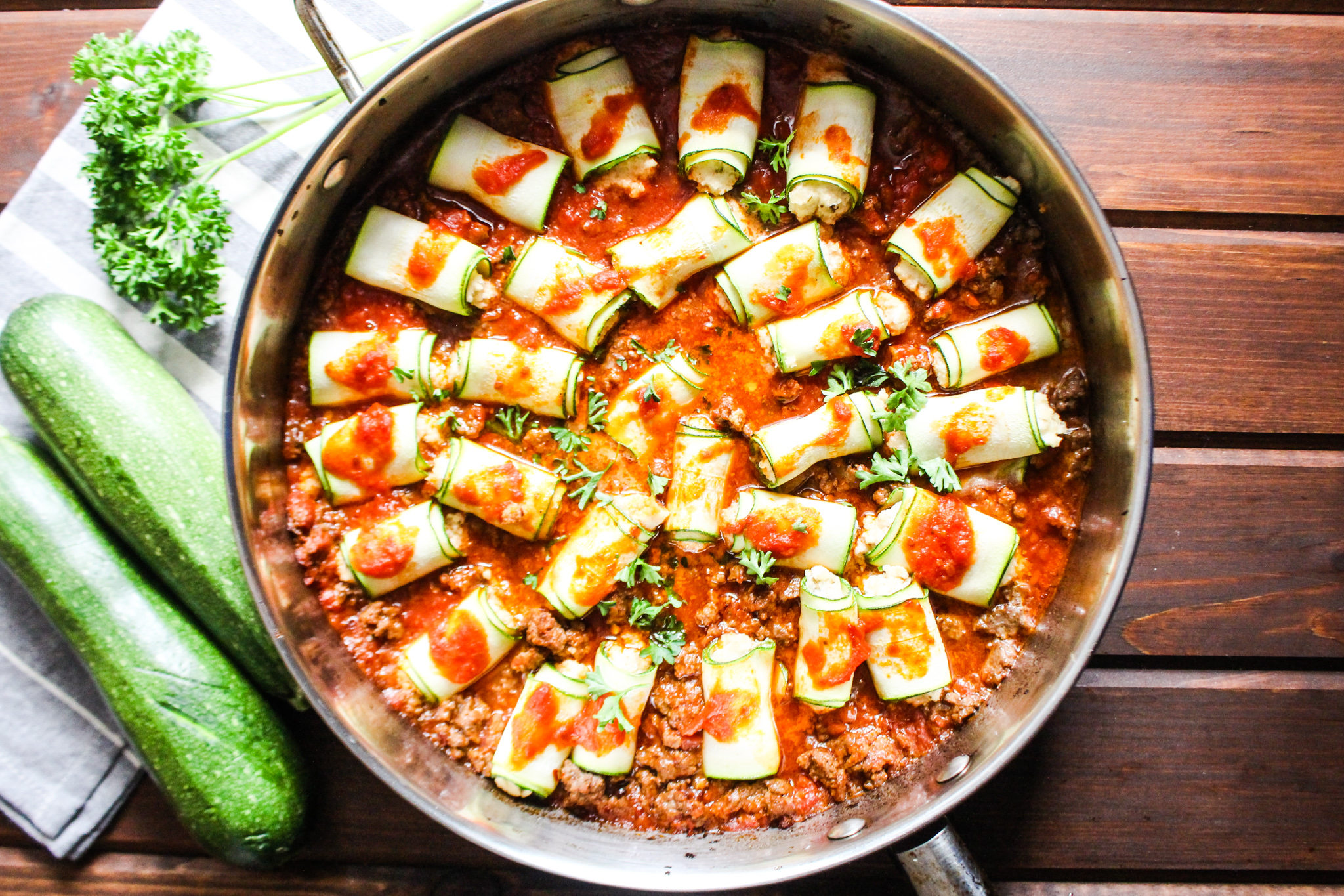 Photo of skillet with zucchini rollatini in red meat sauce.