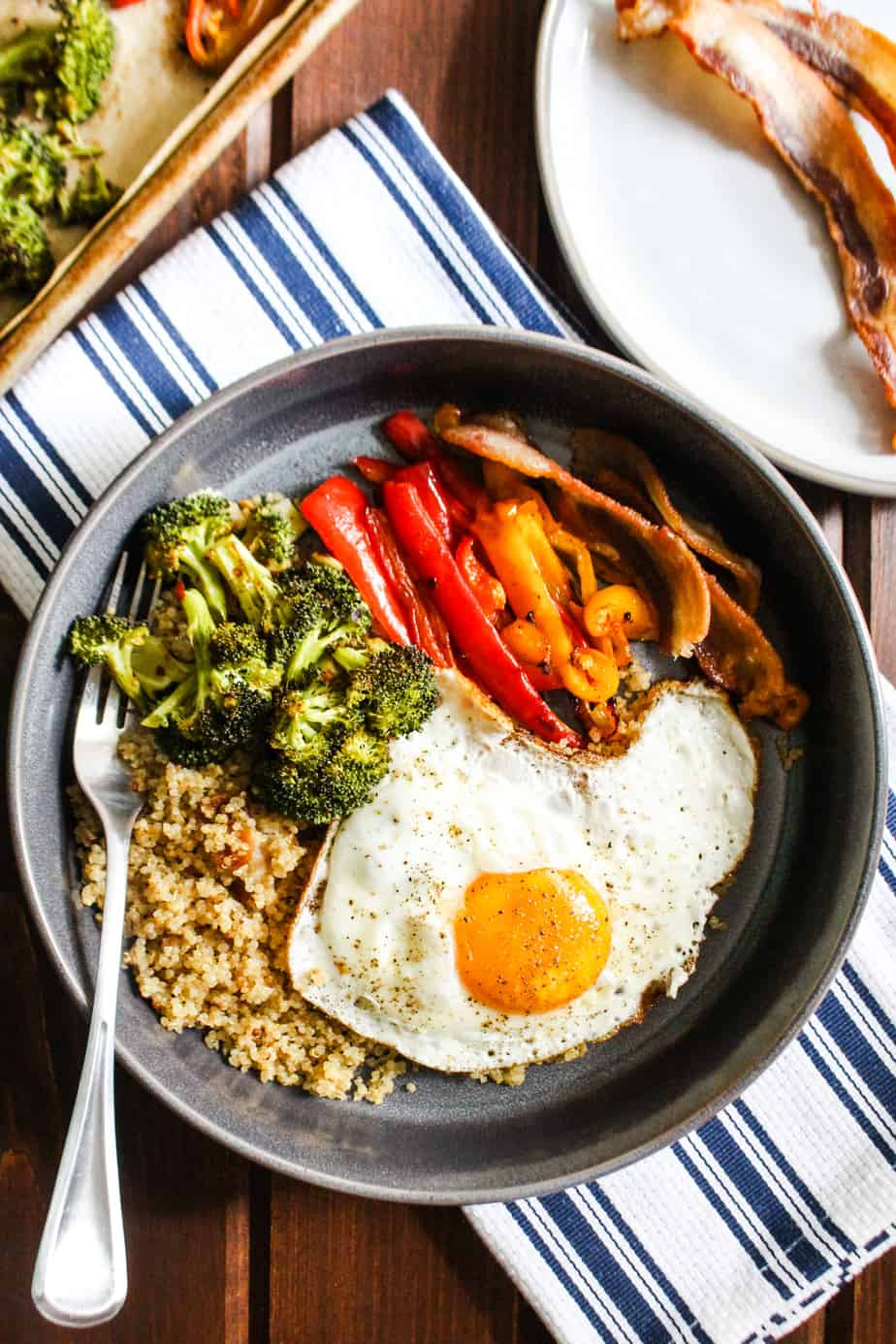 Bowl of quinoa, roasted broccoli, roasted bell peppers, and a fried egg.
