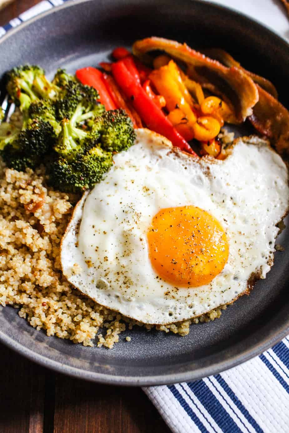 Close up bowl of quinoa, roasted broccoli, roasted bell peppers, and a fried egg.