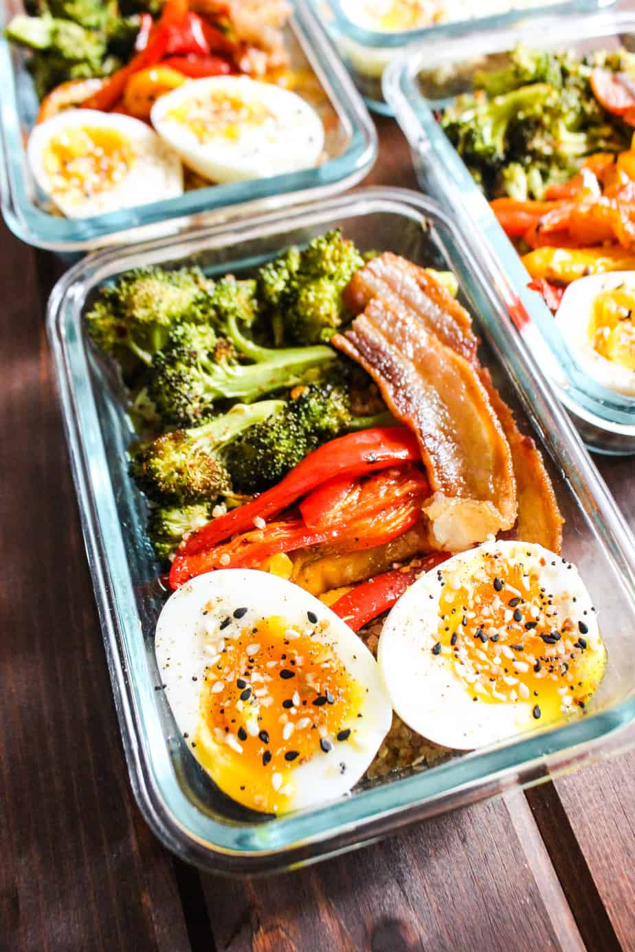 Glass container with roasted broccoli, bell peppers, bacon, and jammy eggs.