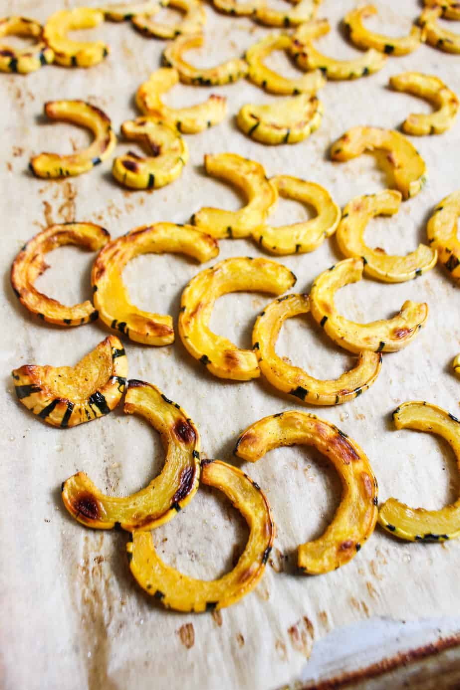 roasted deelicata squash half moons on baking sheet