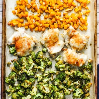 Sheet pan with cooked cubed butternut squash, four chicken thighs, and broccoli