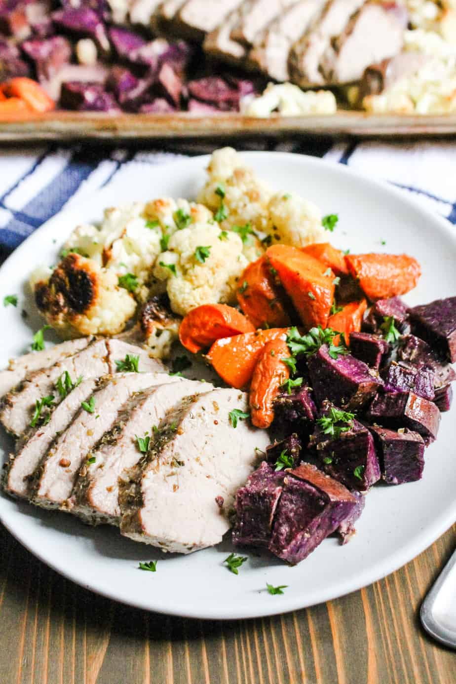 plate with cooked pork, cauliflower, carrots, and purple sweet potatoes
