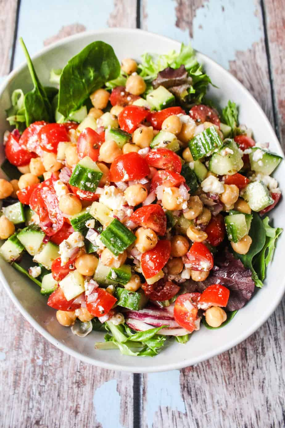 bowl of mixed greens with mediterranean chickpea salad, chickpeas, grape tomatoes, cucumbers, marinated red onions, feta