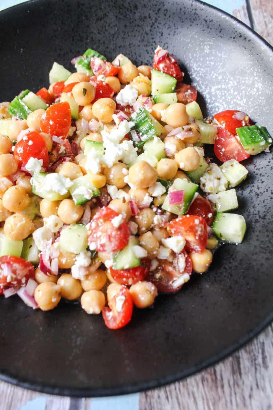 black bowl with chickpeas, cucumbers, grape tomatoes, red onions, feta