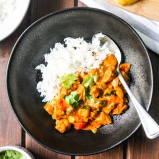 black bowl with white rice and butter chicken and vegetables