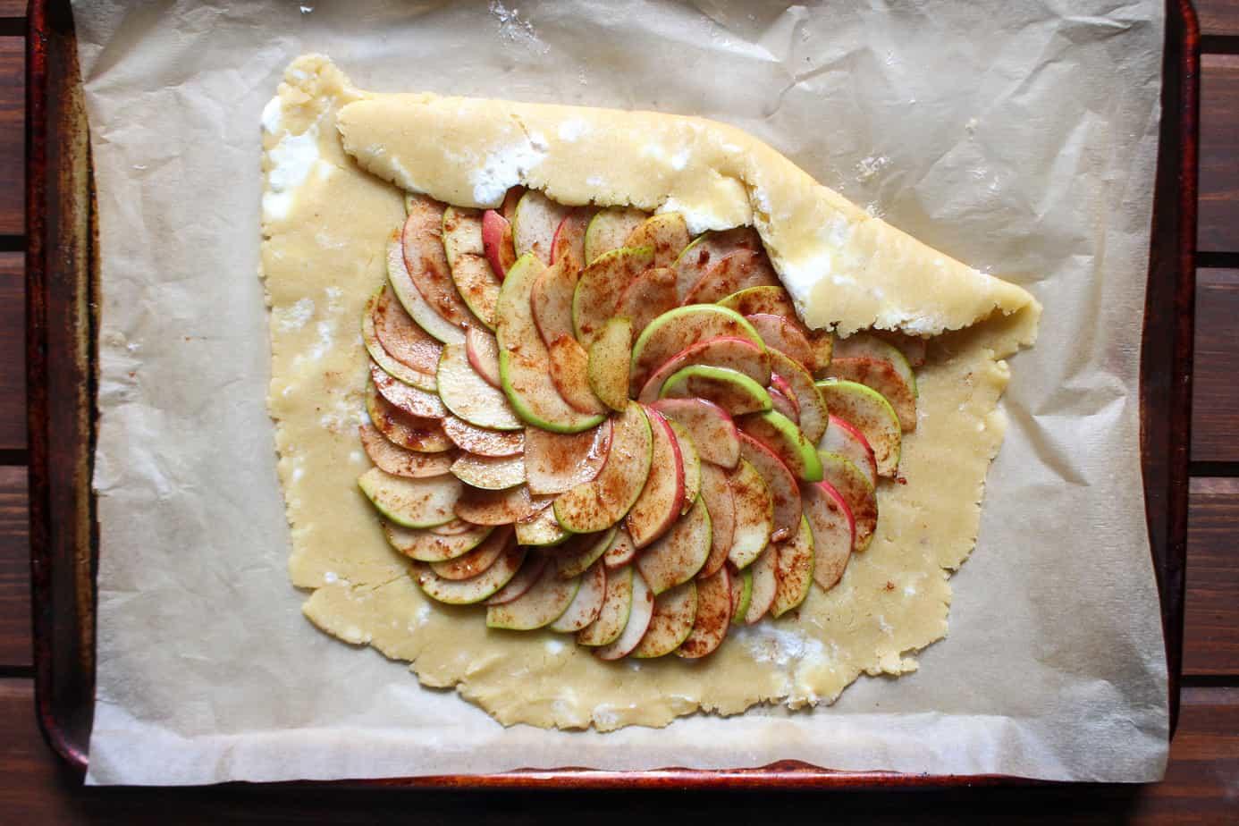 Uncooked cinnamon apple pie galette on sheet pan